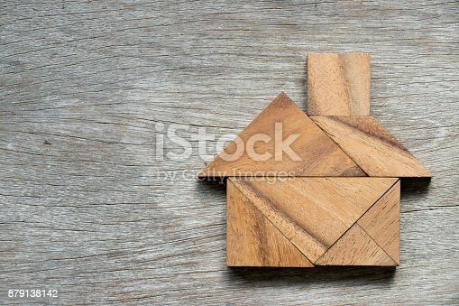 istock Tangram puzzle in home shape on wood background 879138142