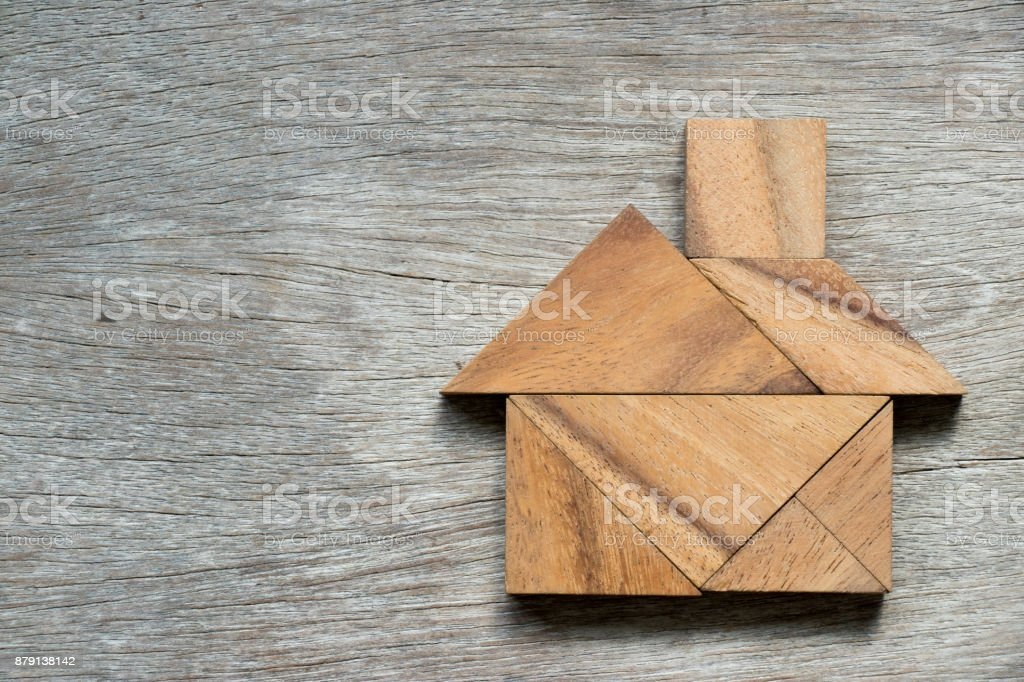 Tangram puzzle in home shape on wood background stock photo