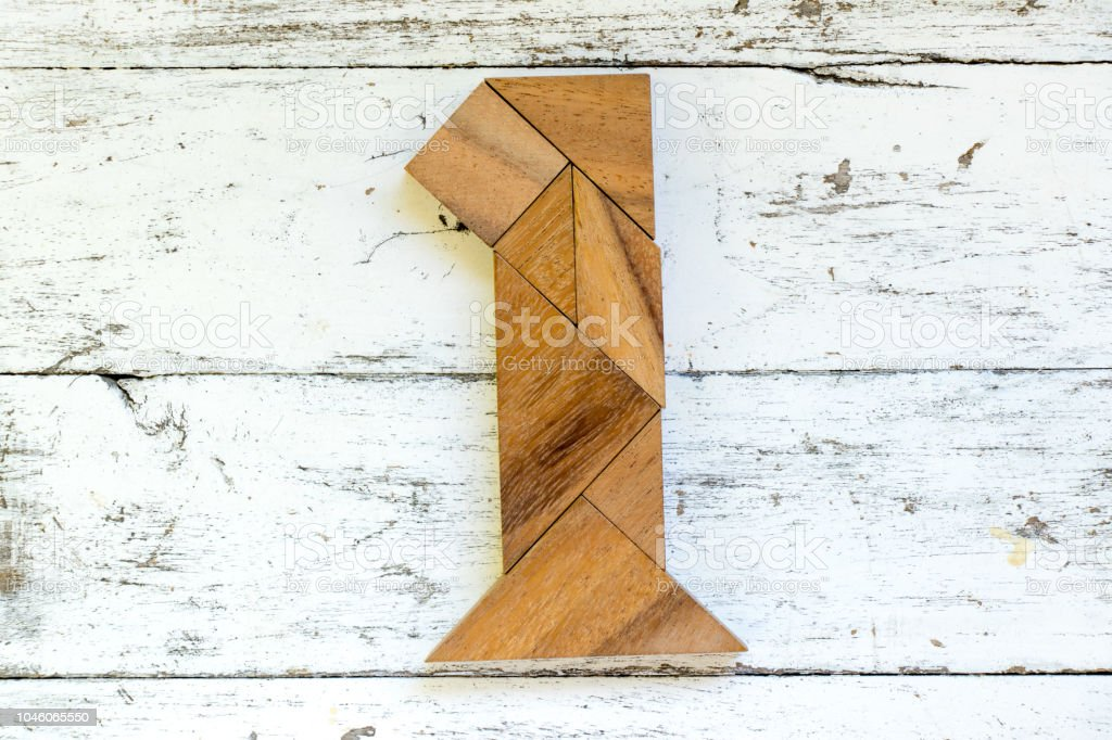 Tangram puzzle in number one shape on old white wood background stock photo