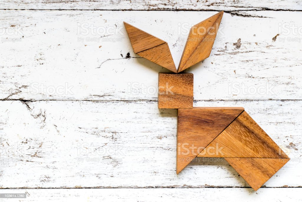 Tangram puzzle in rabbit shape on old white wood background stock photo
