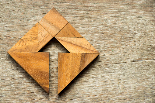 istock Tangram puzzle in square shape with the arrow symbol inside on wood background 848606646
