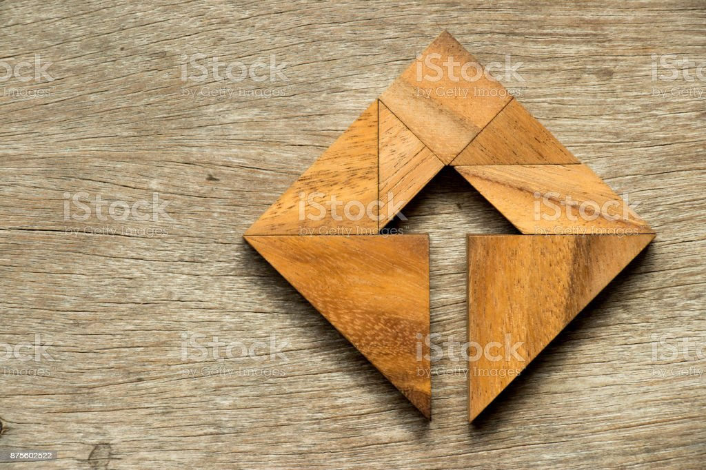 Tangram puzzle in square shape with the arrow symbol inside on wood background stock photo