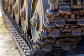view of the front of the caterpillar tank standing on the ground with wheels close up. Military transportation