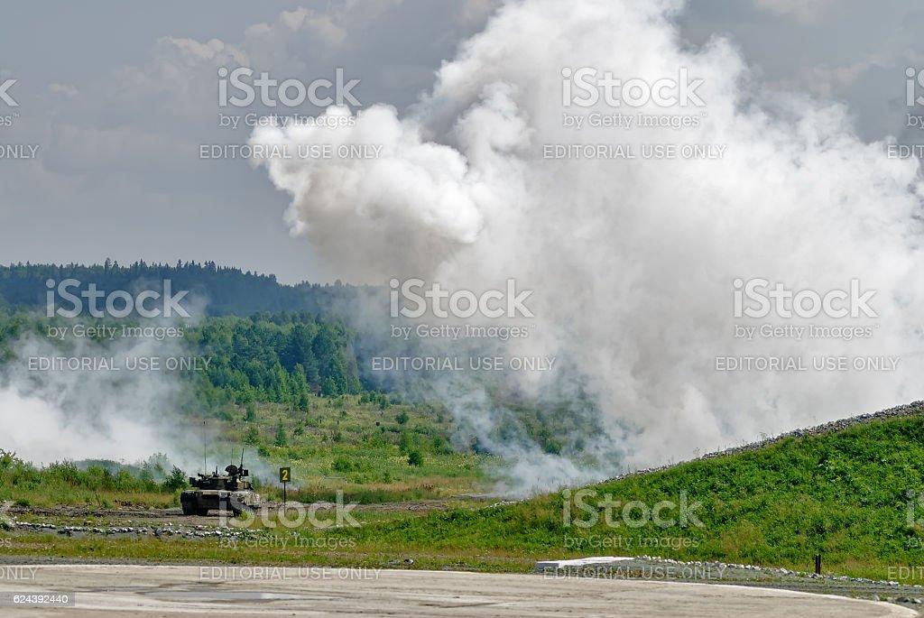 T80 tank hides under smoke screen stock photo