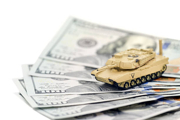 Tank Money A United States tank on one hundred dollar bills. Can represent military spending, investment or waste. money to burn stock pictures, royalty-free photos & images