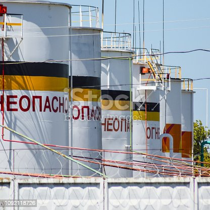Industrial zone, Troitskaya village, Russia - August 9, 2015: Tank the vertical steel. Capacities for storage of oil, gasoline, kerosene and diesel and other liquids. Caption: flammable.