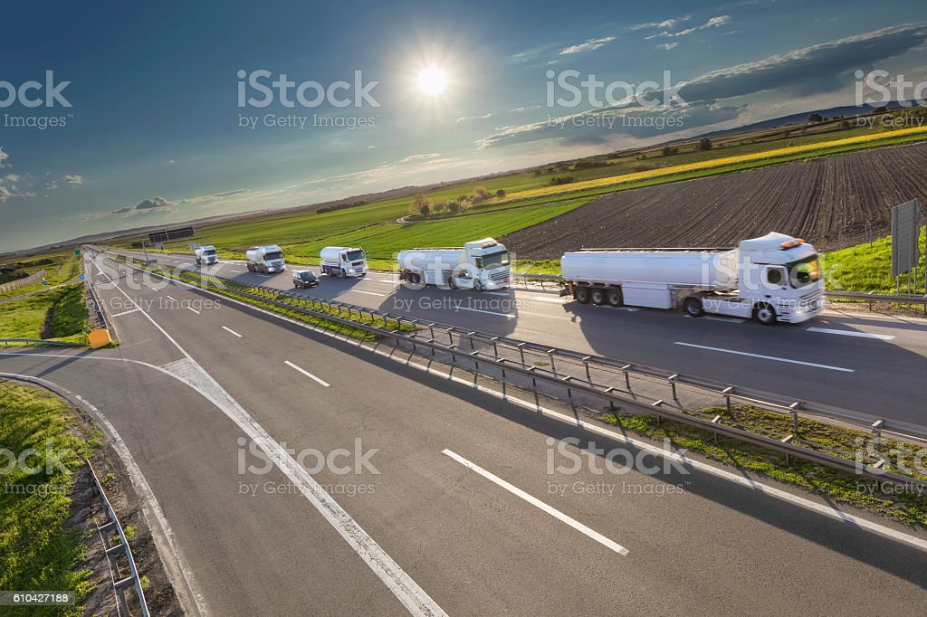 Tank trucks in left driving on highway at sunny day stock photo