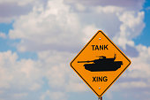 Tank xing crossing sign with humvee on the road