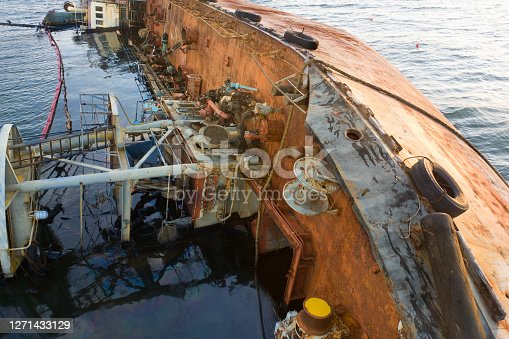 The tanker lies in the water on its side. Petroleum products leak and pollute the environment. Rusty sides of the tanker.