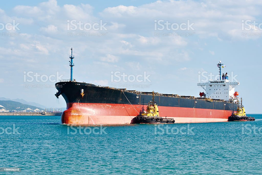 Tanker barge pushed powerful tugboats in sea stock photo