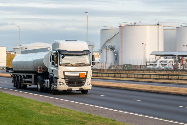 Tanker lorry in motion on the road Tanker truck in motion on the road with oil depot in the background biofuel stock pictures, royalty-free photos & images