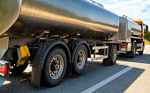 Truck with liquid or oil storage in road or highway of Switzerland. Lorry with service tanker cistern at logistics work. Semi trailer tank. Cargo car drive. Freight delivery. Transport export industry