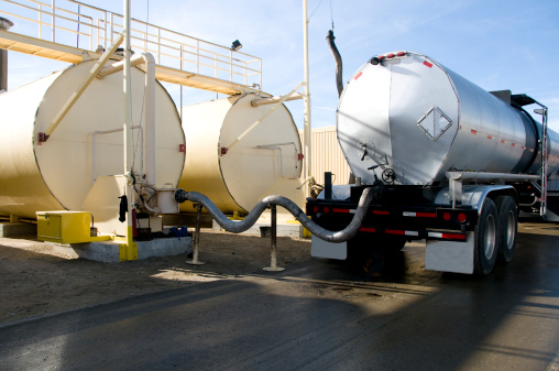 A semi-truck oil tanker is tethered to large oil drums and transfers its oil in to them in this industrial asphalt manufacturing plant.