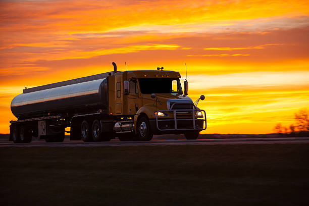 Tanker truck speeding along a highway at sunset. stock photo