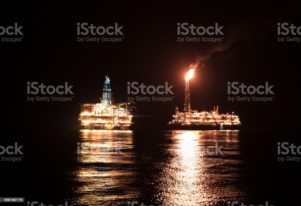 Night view of FPSO tanker vessel near Oil Rig. Offshore oil and gas...