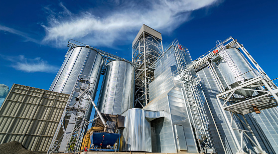 Tanks and agricultural silos of grain elevator storage. Loading facility building exterior. View from below.