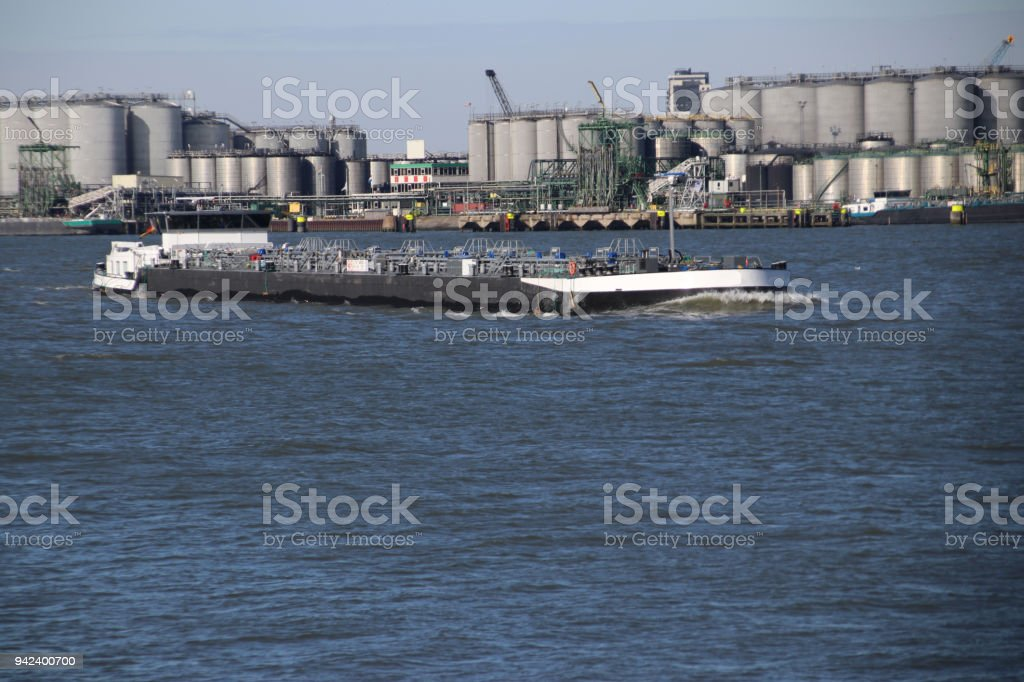 tanks and inland ships in the water of the port of Rotterdam the Netherlands stock photo