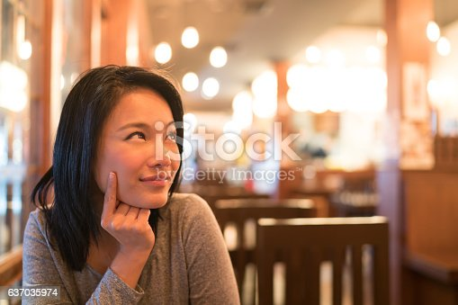 istock Tanned Asian girl looking upward to copy space at restaurant 637035974