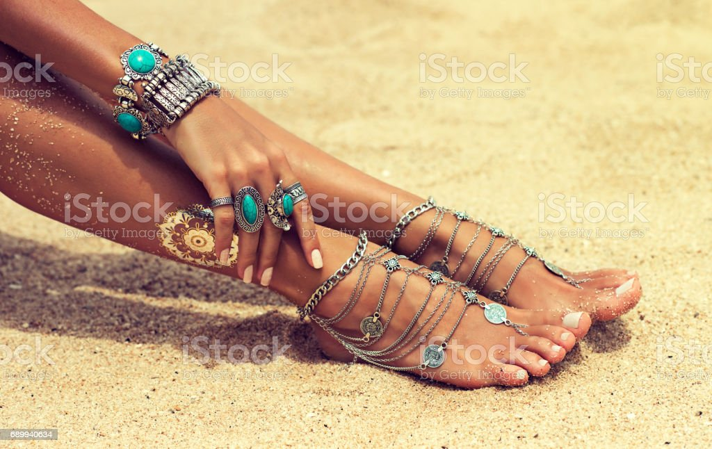 Tanned girl dressed in silver jewelry,bracelets and rings.Boho style. stock photo