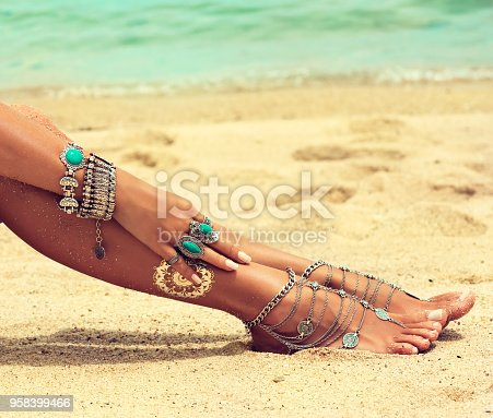 694409862 istock photo Tanned girl dressed in silver jewelry,bracelets and rings.Boho style. 958399466
