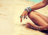 ロータスの位置で日焼けした女の子は銀製の宝石類、ブレスレット、リングに身を包んだ。自由奔放に生きるスタイル。