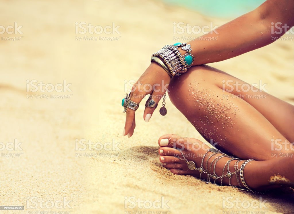 Tanned girl in lotus position dressed in silver jewelry,bracelets and rings.Boho style. stock photo