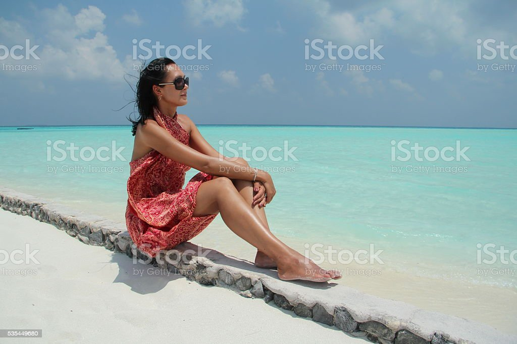 Tanned girl  in red pareo in the Maldivian beach stock photo