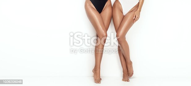 Tanned sexy slim legs of two women on white studio background.