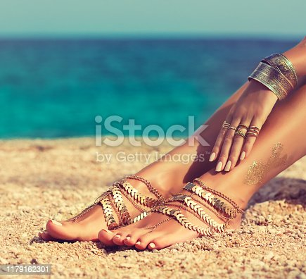 Tanned, slender, well groomed woman's feet dressed in gilded leg bracelets and graceful hand is layng on the knee covered by rings and bangles in Boho style on the background of green water of tropical sea. Body parts.