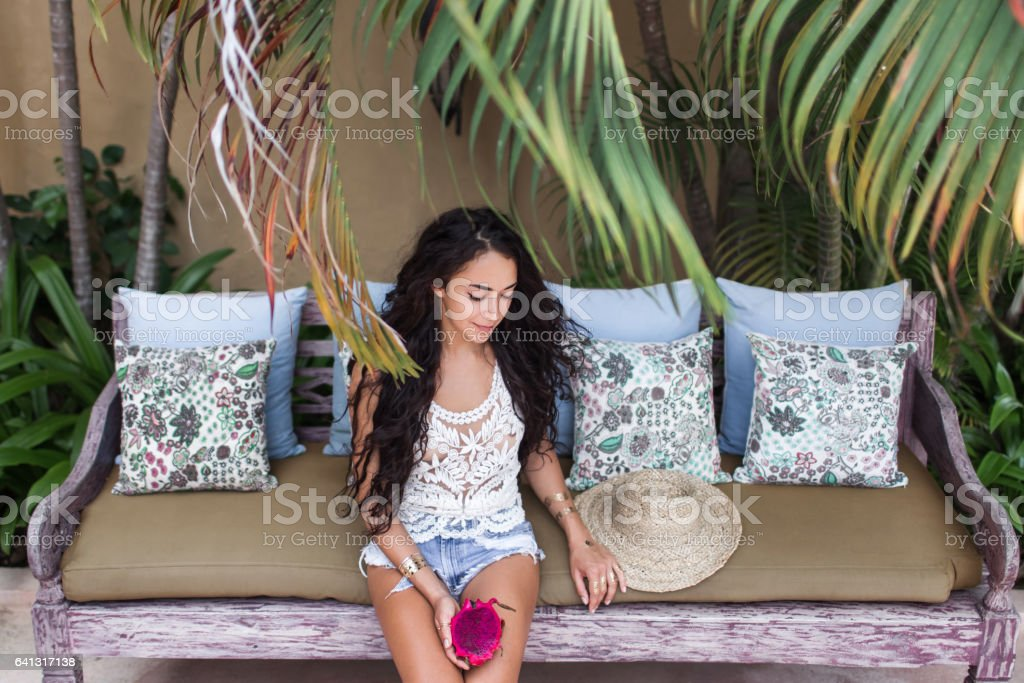 Tanned slim woman legs in jeans short. Hands in gold flash tattoo holding dragon fruit stock photo