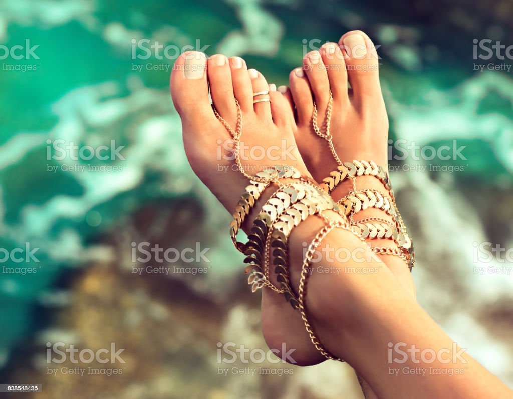 Tanned, well groomed womans feet dressed in leg bracelets in Boho style. stock photo
