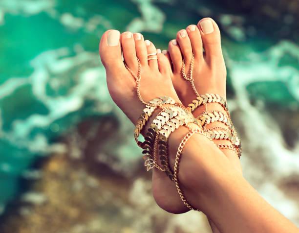 gebräunt, gut präparierte womans füße in bein armbänder im boho-stil gekleidet. - armband water stock-fotos und bilder