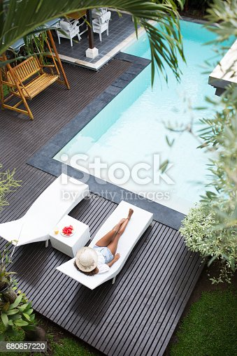[Note for inspector: Photo files for becoming exclusive contributor] Tanned young woman enjoying sunbath near swimming pool. Mixed race woman covering face with hat and relaxing in chaise lounge. Rich woman resting in back yard. Summer concept