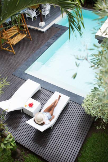 Tanned woman enjoying sunbath near swimming pool stock photo
