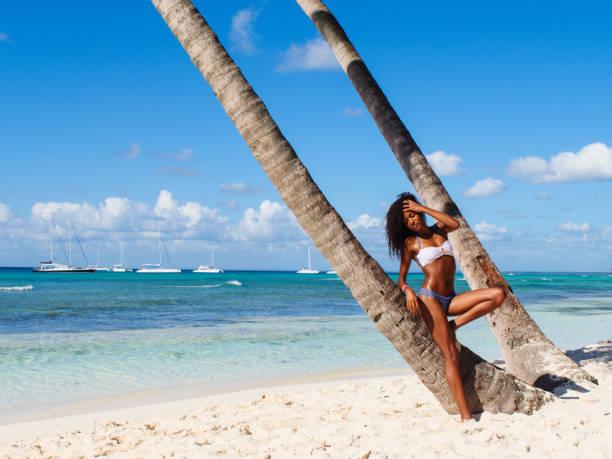 mujer bronceada en la playa tropical - mujeres dominicanas fotografías e imágenes de stock