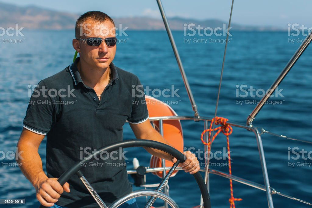 Tanned young male skipper at the helm of a sailing yacht. Lizenzfreies stock-foto