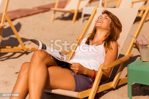 Attractive brunette lying on a sunbed on a beach, reading a magazine and enjoying the sun