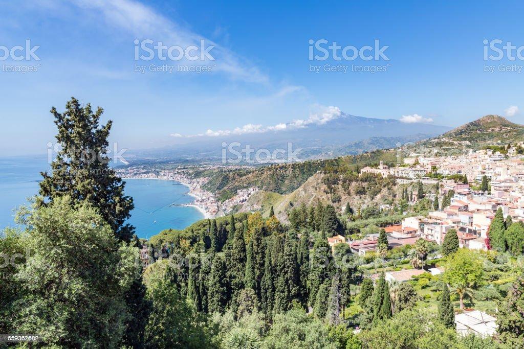 Taormina at Sicilian coast with smoking Etna in the distance stock photo