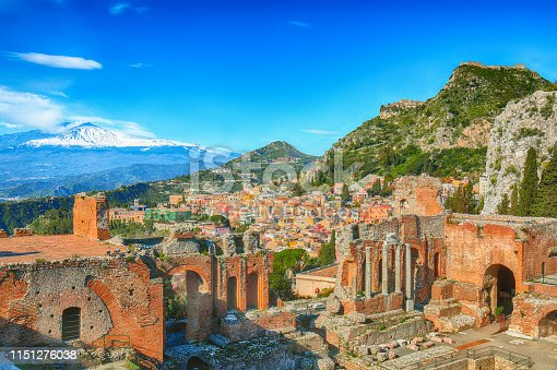 Ruins of ancient Greek theater in Taormina and Etna volcano in the background. Coast of Giardini-Naxos bay, Sicily, Italy, Europe.