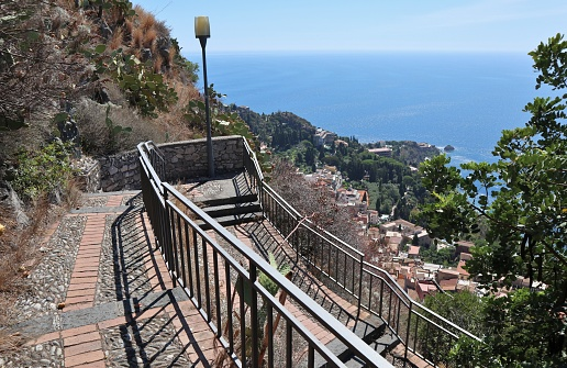 Taormina, Sicily, Italy - August 28, 2020: Panorama from the Via Crucis trail on Monte Tauro overlooking the village