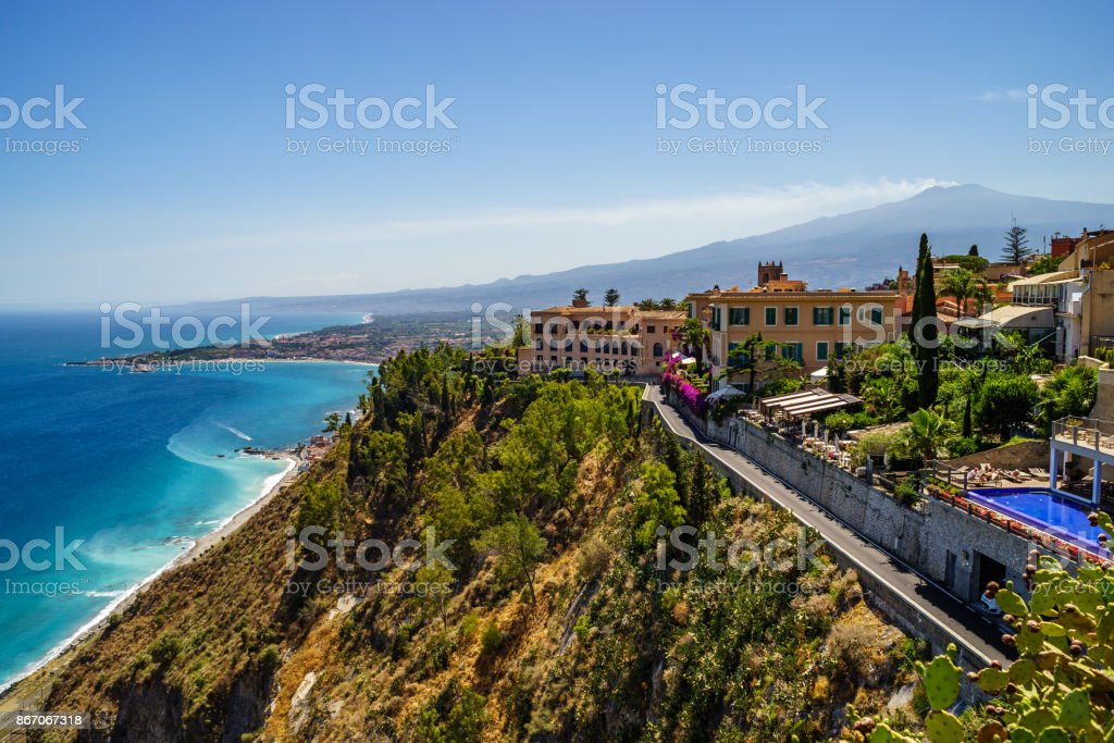 Taormina with the double smoke tail of the Etna extending over the the Giardini-Naxos bay of the Ionian Sea, Sicily stock photo