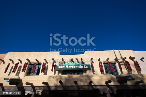 Taos, NM: An old adobe building on the historic Taos Plaza decorated with traditional chili pepper ristras. Vibrant blue sky background with copy space.