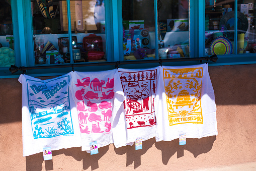 Taos, NM: Colorful towels hang outside a kitchen shop in historic downtown Taos, against an adobe wall.