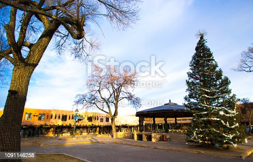 Taos, NM: The historic Taos Plaza in early morning winter light, with a Christmas tree and bandstand. Copy space in the blue sky.