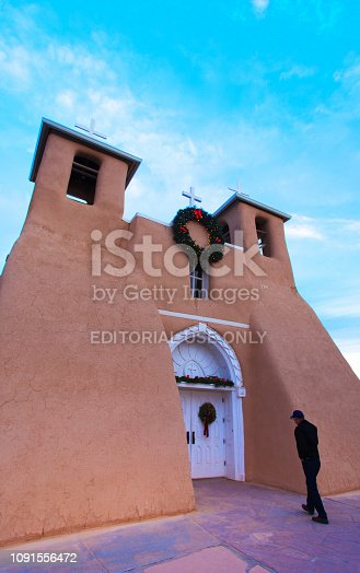 Taos, NM: A man approaches the Ranchos de Taos church (San Francisco de Asis Mission Church) in winter morning light, with the shadow of a cross on the facade. Completed in 1816, the adobe church is located just outside Taos, New Mexico. Copy space in the blue sky.