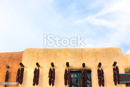 Taos, NM Plaza: Old adobe buildings on the Taos Plaza decorated with chili pepper ristras. Vibrant blue sky background with copy space available.