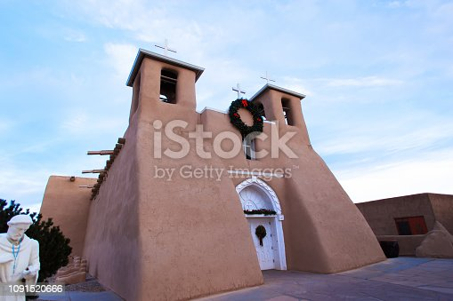 Taos, NM: Ranchos de Taos church (San Francisco de Asis Mission Church) in winter morning light. Completed in 1816, the adobe church is located just outside Taos, New Mexico. Copy space in the blue sky.