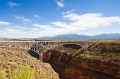 Taos, NM: Rio Grande Gorge Bridge under blue cloudy sky. The bridge, finished in 1965,  is on US 64 and the seventh highest bridge in the US.