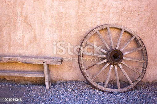 Taos, NM Style: Old Wood Wagon Wheel Against Adobe Wall. Copy space available.