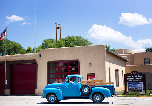 Taos, NM: A vintage turquoise pickup truck stopped in front of the Taos Fire Station.